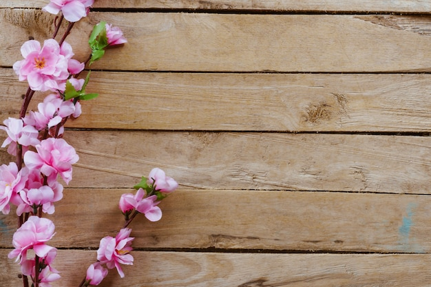 Cherry blossom and artificial flowers on vintage wooden background with copy space. Premium Photo