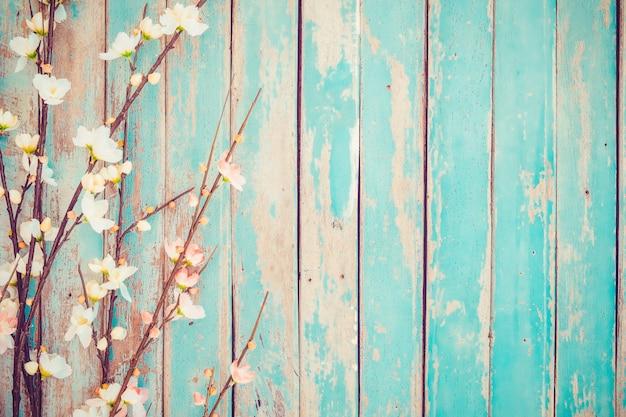 Cherry blossom flowers on vintage wooden background, border design. Premium Photo