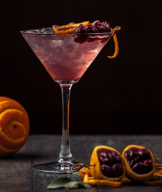 Cherry cocktail garnished with cherry and orange zest and ice Free Photo
