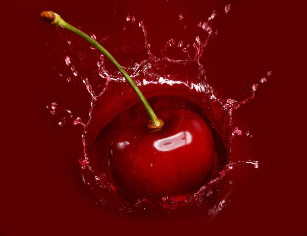 Cherry falling into the lot of juice Free Photo