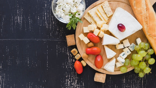 Cherry tomatoes, grapes, cheese blocks and baguette on round chopping board over the textured backdrop Free Photo