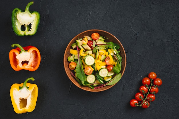 Cherry tomatoes; halved bell pepper and fresh vegan salad on concrete backdrop Free Photo