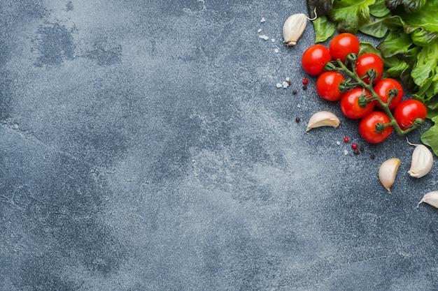 枝にチェリートマト新鮮なハーブとニンニクは暗い石のテーブルの上のスパイスでクローブします。 Premium写真