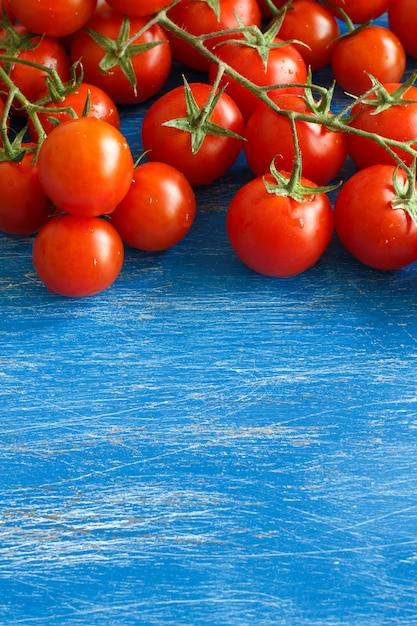 古い青い木製のテーブルのチェリートマトをクローズアップ Premium写真