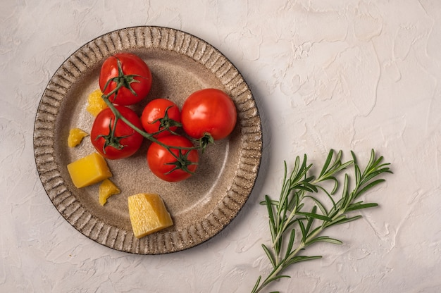 Cherry tomatoes, parmesan cheese on a ceramic plate and rosemary twig on light textured background Premium Photo