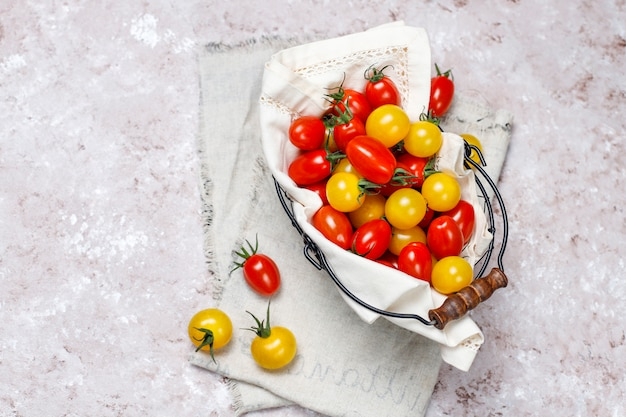 Cherry tomatoes of various colors,yellow and red cherry tomatoes in a basket on light background Free Photo
