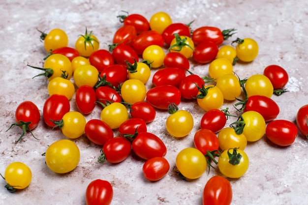 Cherry tomatoes of various colors,yellow and red cherry tomatoes on light background Free Photo