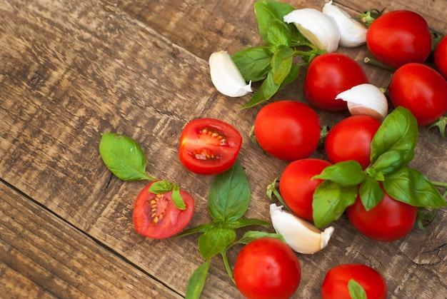 Cherry tomatoes with basil leaves and garlic. Premium Photo