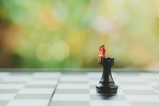 Chess analysisの上に座っているミニチュアのビジネスマンビジネスについてコミュニケーション Premium写真