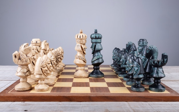 Chess board with pieces of collection put in order and the kings faced Premium Photo