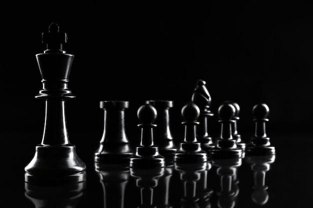 Chess figures on dark black background close up Premium Photo