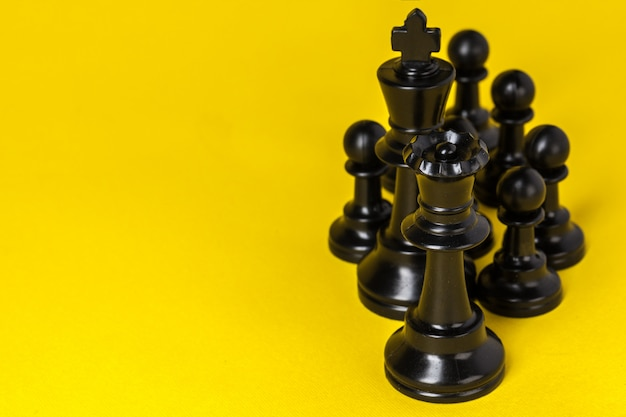 Chess figures on yellow background top view copy space Premium Photo