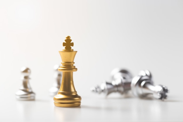 Chess game gold king standing and silver background, business strategy concept. Premium Photo