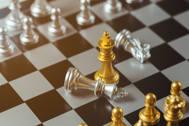 Chess game gold king standing and silver chessboard, business strategy concept. Premium Photo