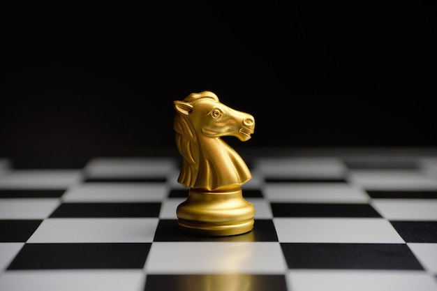 Chess gilded horse piece on the board. Premium Photo