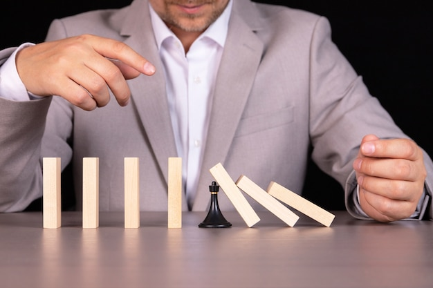 A chess pawn stops a wooden domino from falling Premium Photo