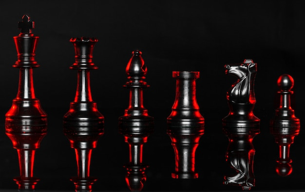Chess pieces on dark background with red backlight Premium Photo