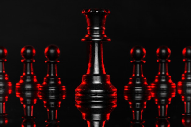 Chess pieces on dark  with red backlight close up Premium Photo