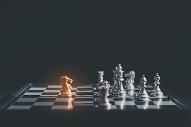 Шахматные фигуры рыцари друг против друга на шахматной доске. Premium Фотографии