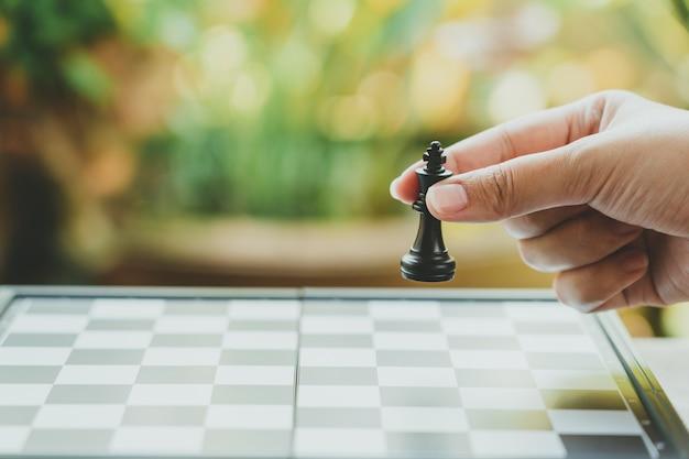 背景としてチェス王を保持している実業家がchessboard.usingに配置されます。 Premium写真