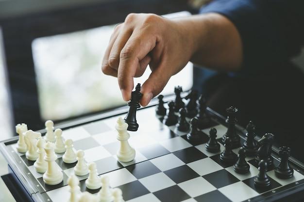 チェス王を保持している実業家は、chessboard.usingに配置されます。 Premium写真