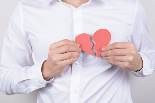 Chest pain ache attack heartache health unhealthy care healthcare problem concept. cropped close up  of small heart in hands isolate grey wall Premium Photo