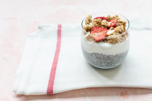 Chia pudding with almond milk, yogurt, and dried strawberries Premium Photo