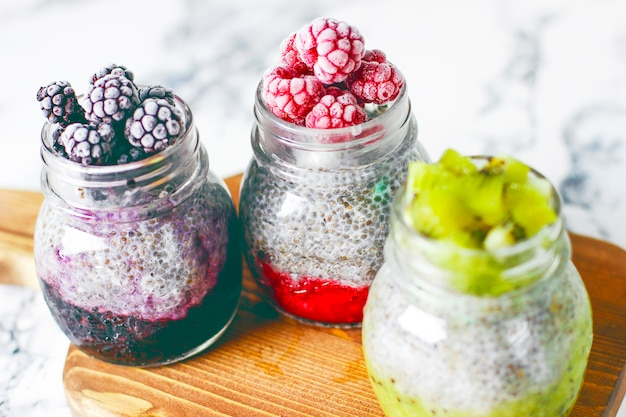 Chia pudding with berries,  raspberry sauce, kiwi sauce, blackberry sauce and frozen raspberries Premium Photo