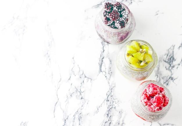 Chia pudding with berries,  raspberry sauce, kiwi sauce, blackberry sauce Premium Photo