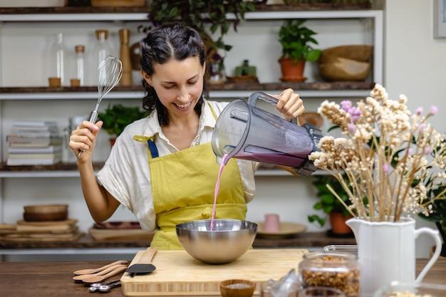 チアプリンの調理工程。アーモンドミルクにドラゴンフルーツピンクのナチュラルカラーエキスとチアシードを混ぜたもの。 無料写真