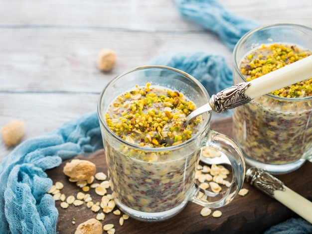 Chia rolled oat pudding overnight porridge with quinoa, banana, pistachio nuts, milk. one cup healthy breakfast Premium Photo