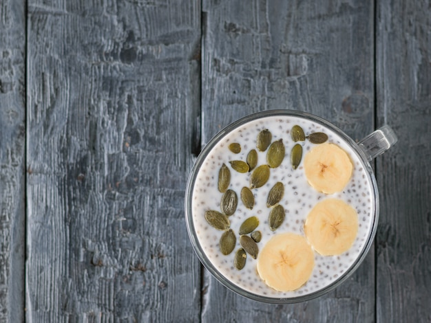 Chia seed pudding with banana and pumpkin seed on a dark wooden table. the view from the top. flat lay. Premium Photo