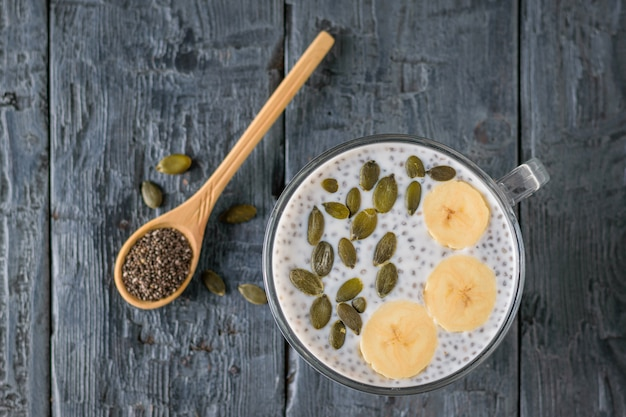 Chia seed pudding with banana and wooden spoon on dark wooden table. the view from the top. flat lay. Premium Photo