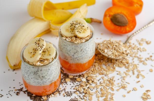 Chia seed pudding with greek yogurt, banana, oats and fresh apricot. Premium Photo