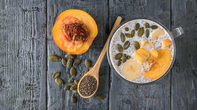 Chia seed pudding with peach and pumpkin seed on a dark wooden table. the view from the top. flat lay. Premium Photo
