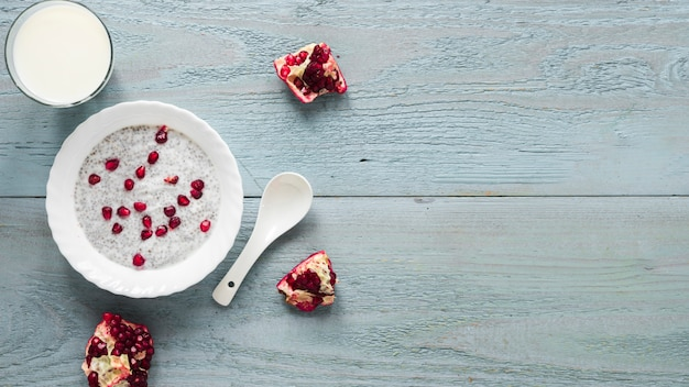 Chia seed pudding with seeds of pomegranate in white bowl with spoon Free Photo