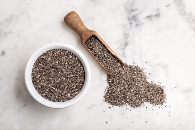 Chia seeds in wooden scoop and bowl on marble table. salvia hispanica. copyspace, top view Premium Photo