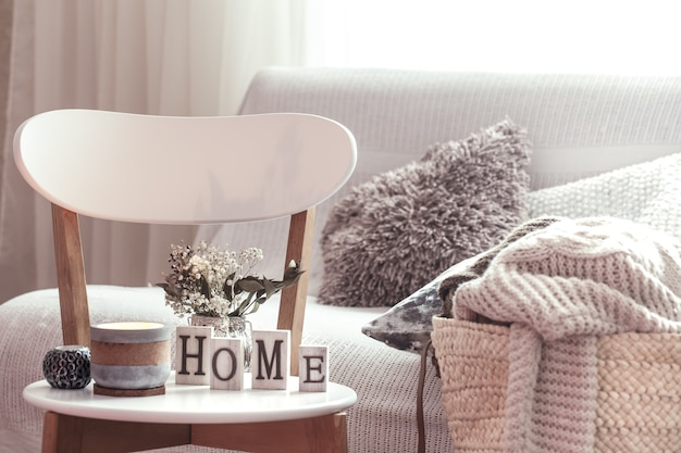 Chic interior for a house. candles, a vase with flowers with wooden letters of the home on wooden white chair. sofa and wicker basket with cushions in the background. home decoration. Free Photo