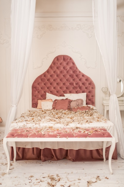 Chic retro king size bed strewn with feathers from the pillow, pillow fight in the room. Premium Photo