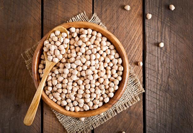 木製のテーブルの上椀のひよこ豆をクローズアップ 無料写真