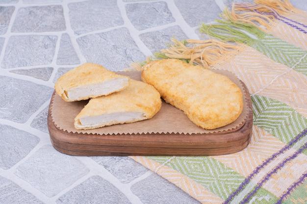 木の板にチキンと魚のナゲット。 無料写真