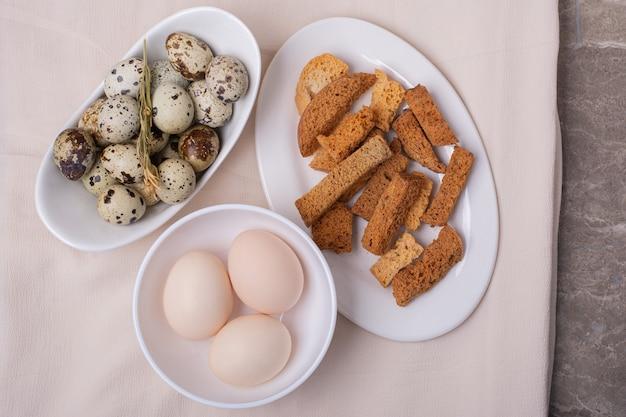 크래커와 함께 흰색 컵에 닭고기와 메추라기 달걀 무료 사진