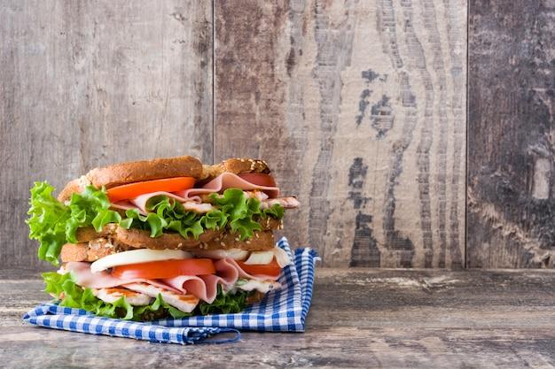 木製のテーブルコピースペースにチキンと野菜のサンドイッチ Premium写真