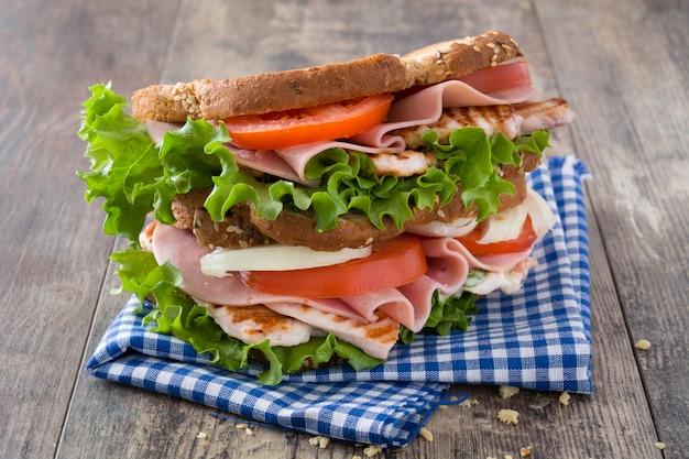 木製のテーブルにチキンと野菜のサンドイッチ Premium写真