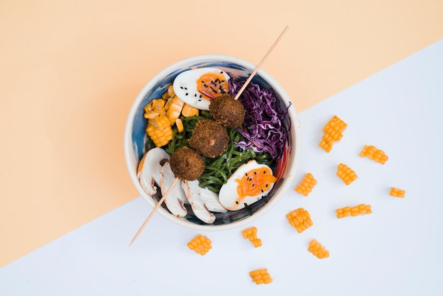 Chicken balls in stick over the bowl with salad and eggs on dual background Free Photo