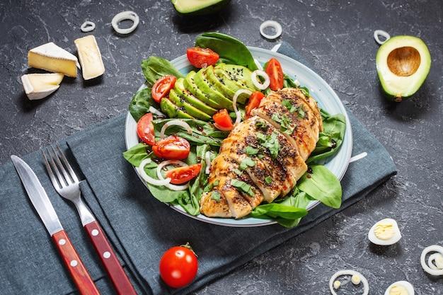 시금치와 체리 토마토를 곁들인 닭 가슴살과 아보카도 샐러드 프리미엄 사진