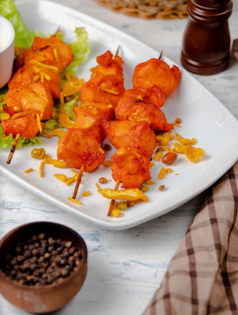 Chicken breast bbq, shish kebab with vegetables, herbs and sumakh in white plate. Free Photo