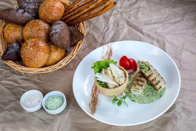 Chicken breast fingers filled with herbs sauce, served with rice and bread Free Photo