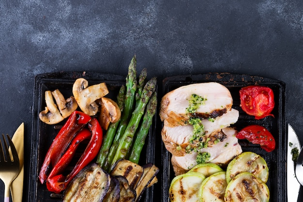 Chicken breast grill with bbq vegetables and pesto sauce in a cast iron pan on concrete Premium Photo
