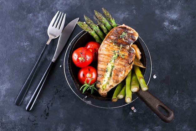 Chicken breast grill with bbq vegetables and pesto sauce in a cast iron pan on a stone Premium Photo